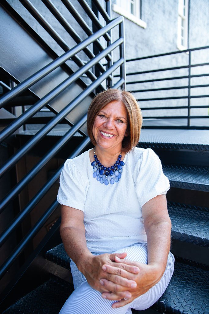 Lisa Zilli sitting on stairs in office building